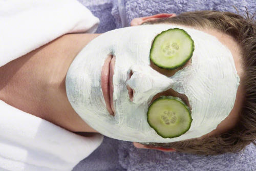 Man getting a facial with cucumber slices
